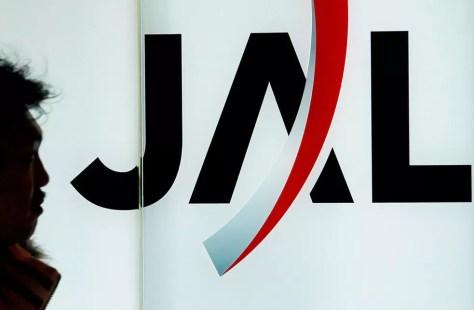 Passageiro caminha ao lado do logotipo da Japan Airlines, no aeroporto de Haneda, em Tóquio, em imagem de 8 de janeiro de 2010  — Foto: Itsuo Inouye/ AP