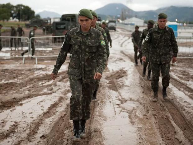 Soldados caminham na lama no Campo da fé em Guaratiba (Foto: Nicolas Tanner/AP)