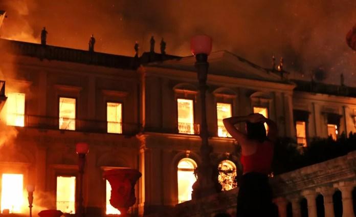 Uma mulher reage ao ver o incêndio no prédio do Museu Nacional, no Rio de Janeiro, na noite de domingo (2) (Foto: Ricardo Moraes/Reuters)