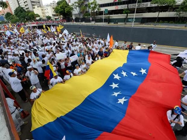 Manifestantes com bandeira da Venezuela tomam ruas de Caracas em protesto contra Nicolas Maduro (Foto: Federico Parra / AFP)