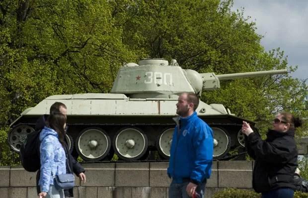 Turistas passam por tanques soviéticos da Segunda Guerra Mundial expostos em memorial em Berlim nesta terça-feira (15) (Foto: John Macdougall/AFP)