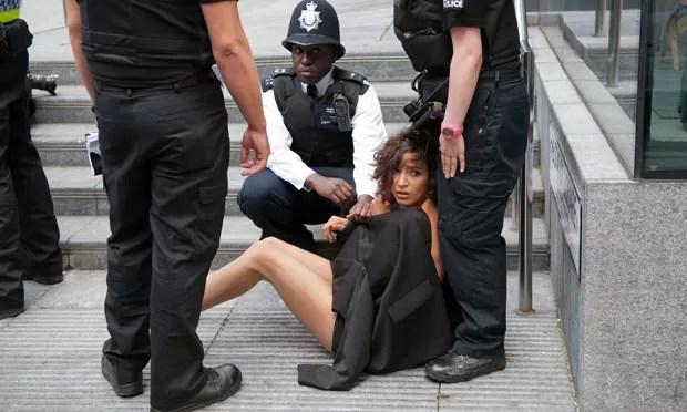 Mulher membro do Femen é coberta por policiais após ser detida em Londres. (Foto: Will Oliver/AFP)