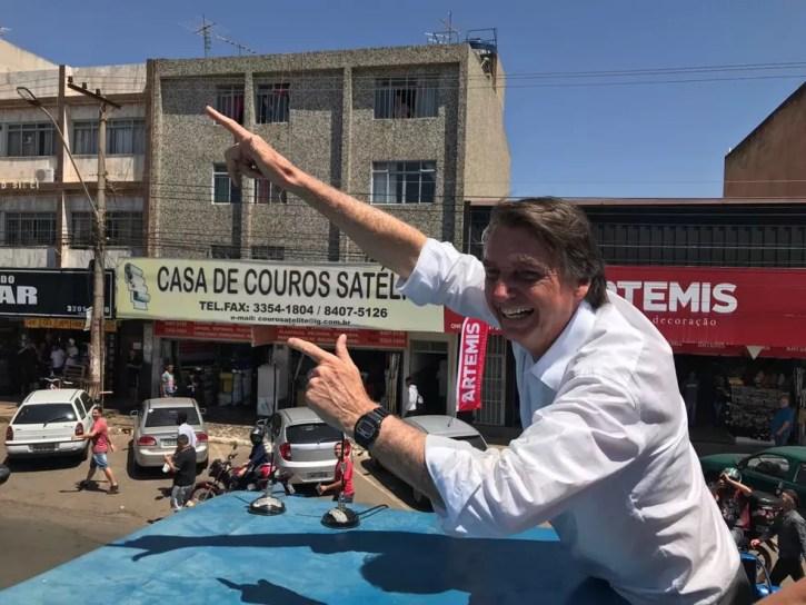 O candidato a presidente pelo PSL, Jair Bolsonaro, faz gesto representando uma arma durante carreata em Ceilândia, no Distrito Federal — Foto: Fernanda Calgaro / G1