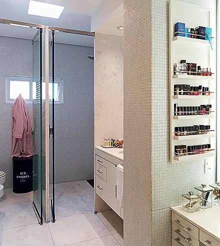 Banheiro do casal | Com cubas individuais, o ambiente tem piso de mármore branco piguês e parte das paredes revestida com pastilhas de vidro (Foto: Victor Affaro e Carlos Andres Varela)