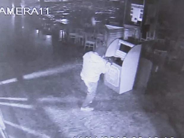 Assaltante se prepara para colocar explosivo em caixa (Foto: Reprodução/TV TEM)