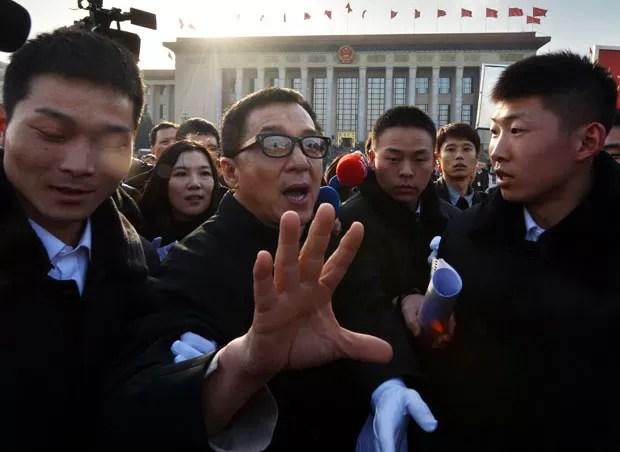 Jackie Chan causa tulmuto na saída do Grande Palácio de Pequim (Foto: Mark Ralston/AFP)