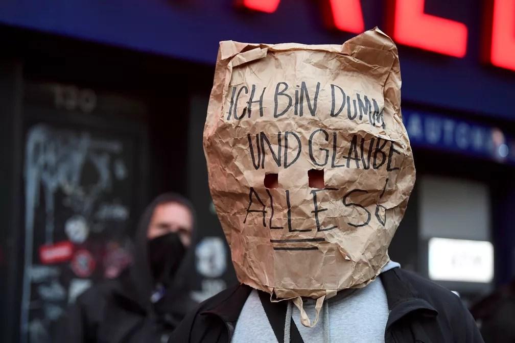 Manifestante usa saco de papel com a mensagem 'Sou burro e acredito em tudo!' durante protesto em Hamburgo, na Alemanha — Foto: Fabian Bimmer/Reuters