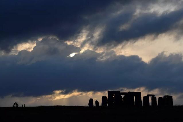 Agentes de segurança patrulham o perímetro do círculo de pedras de Stonehenge durante o por do sol, onde as celebrações oficiais do Solstício de Verão foram canceladas devido à propagação da doença por coronavírus (Covid-19), perto de Amesbury, na Grã-Bretanha, em junho de 2020 — Foto: Toby Melville/Reuters/Arquivo