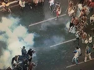 Indígena mira flecha antes de acertar perna de policial durante protesto em Brasília (Foto: Reprodução/TV Globo)