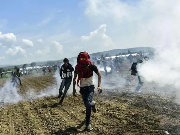 Refugiados fogem do gás lacrimogênio lançado pela polícia da Macedônia em Idomeni, na Grécia, na fronteira entre os dois países (Foto: Bulent Kilic/AFP)