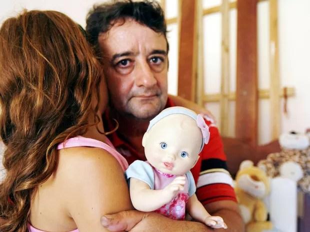 Ubiratan Homsi com sua filha de 10 anos, que teria sido estuprada pelo padre (Foto: Paulo Araújo / Agência O Dia / Estadão Conteúdo)