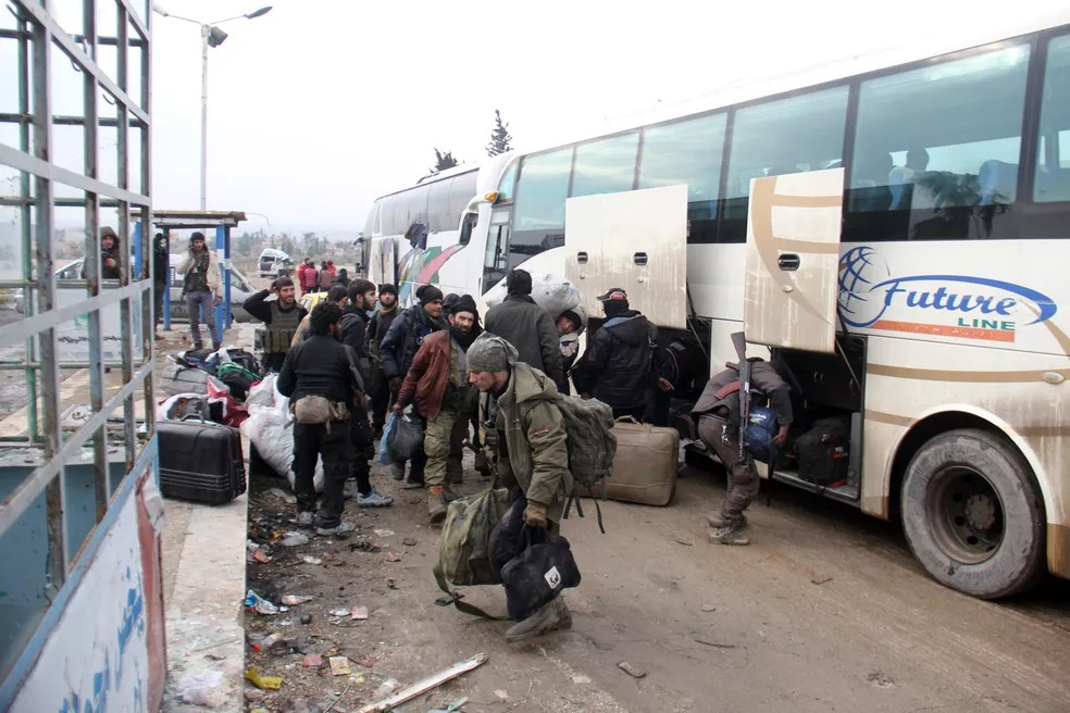Rebeldes sírios chegam nesta quinta-feira (22) em área controlada pelo regime após serem retirados de Aleppo (Foto: Omar haj kadour / AFP)
