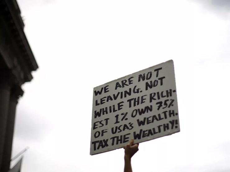 'Não vamos sair. Não enquanto os 1% mais ricos tiverem 75% da riqueza dos EUA. Taxem os ricos!', diz cartaz em protesto contra 'ganância corporativa' em Wall Street — Foto: Reuters / Eric Thayer