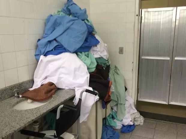 Roupas hospitalares acumuladas no banheiro onde os acompanhantes dos pacientes tomam banho (Foto: Cristina Boeckel/ G1)
