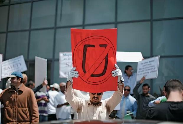 IMPOPULAR Taxistas protestam diante da sede  do Uber, na Califórnia.  O serviço é acusado  de concorrência desleal (Foto: Lucy Nicholson/Reuters)