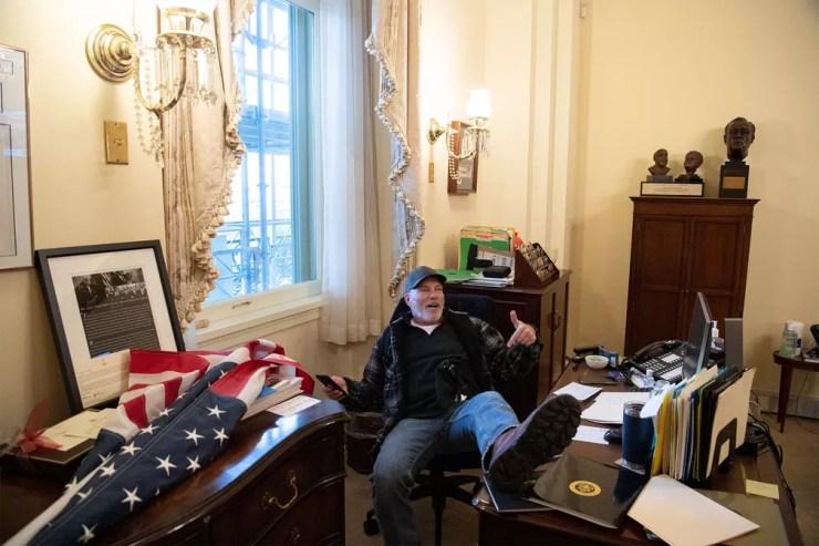 Apoiador de Donald Trump posa sentado na cadeira da parlamentar democrata Nancy Pelosi em seu gabinete no Capitólio após invasão — Foto: Saul Loeb/AFP