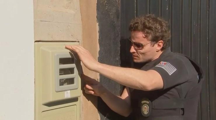 Policial fiscaliza caixa de energia em casa na região de Birigui (Foto: Reprodução/TV TEM)