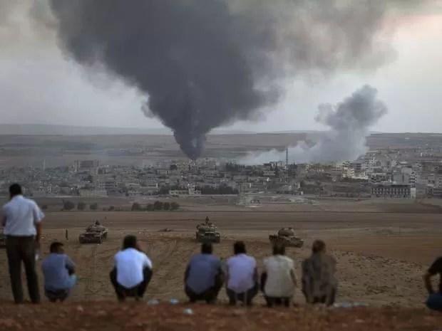 Fumaça em cidade síria de Kobani é vista por curdos turcos perto de fronteira com a Turquia nesta quinta-feira (9) (Foto: REUTERS/Umit Bektas)