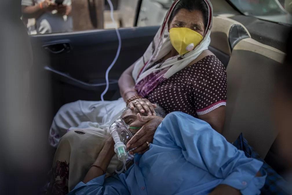 Homem recebe oxigênio dentro de carro em Nova Delhi, na Índia, no sábado (24) — Foto: Altaf Qadri/AP