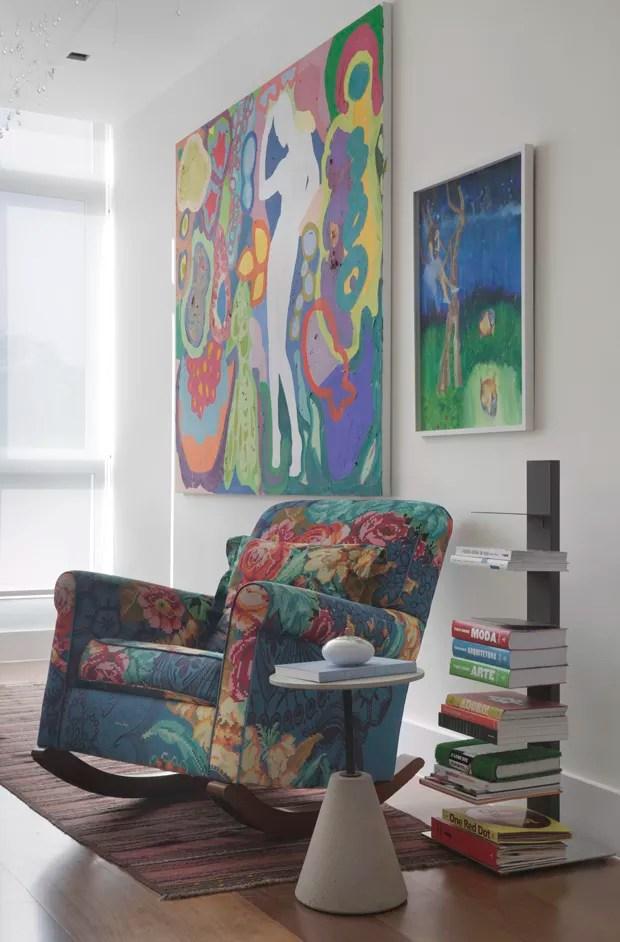 CANTO DE LEITURA | A poltrona floral e os quadros pertenciam ao acervo da família. Mesa lateral, estante de livros e o tapete são peças da LZ Studio (Foto: Denilson Machado - MCA Estúdio/Divulgação)