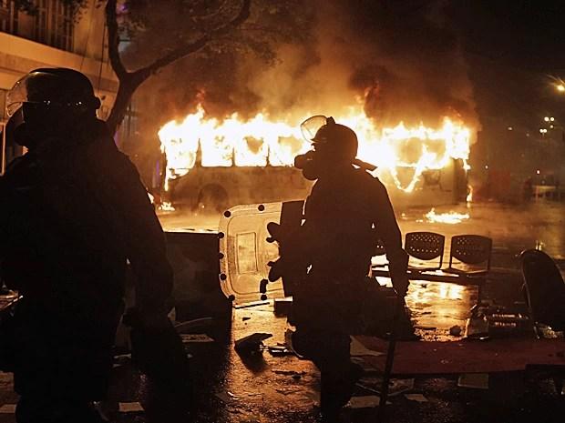 7 de outubro - Policial caminha em frente a ônibus queimado por black blocs durante protesto no Rio. A manifestação é para exigir mudanças no sistema de ensino público estadual e municipal. (Foto: Ricardo Moraes/Reuters)