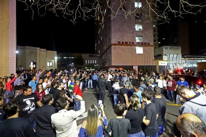 Pessoas fazem oração diante da Santa Casa de Juiz de Fora para onde Jair Bolsonaro foi levado depois de ter sido esfaqueado, em Minas Gerais (Foto: Fábio Motta/Estadão Conteúdo)
