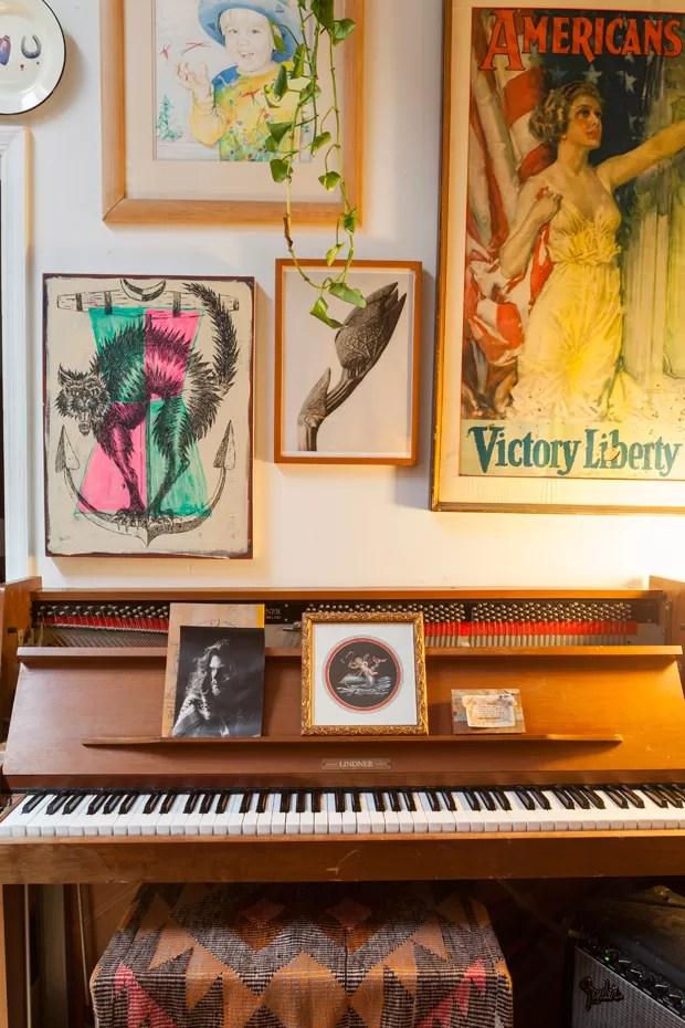 No piano, uma foto de Gabriel como modelo. Na parede, um desenho dele quando criança e outros quadros, também achados na rua. (Foto: Lufe Gomes/Life by Lufe)