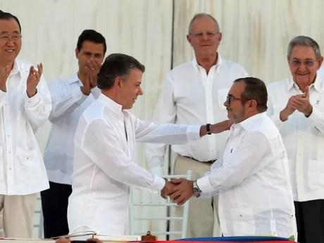 Juan Manuel Santos, presidente da Colômbia, e Rodrigo Londoño, chefe das Farc, se cumprimentam nesta segunda-feira (26) após assinar o acordo de Paz em Cartagena (Foto: Fernando Vergara/AP)