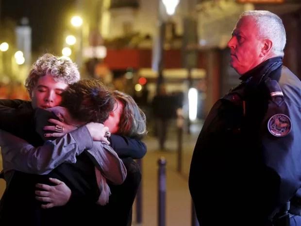 Trio se abraça perto da casa de shows Bataclan após ataque terrorista em Paris (Foto: Christian Hartmann/Reuters)