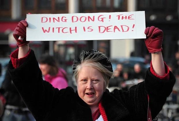 Com cartaz 'a bruxa está morta', mulher comemora a morte de Margaret Thatcher nesta segunda-feira (8) em Londres (Foto: AFP)