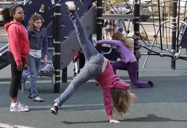 Ryan faz acrobacias com suas amigas no recreio do colégio, num subúrbio de Chicago; nascida menino, ela se identifica como menina desde os primeiros anos de vida (Foto: AP Photo/M. Spencer Green)
