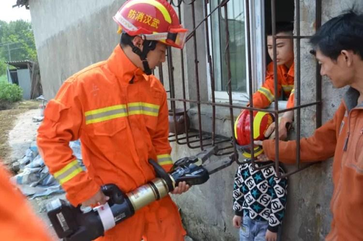 Menino foi resgatado após entalar cabeça em grade de janela na China (Foto: Reuters)