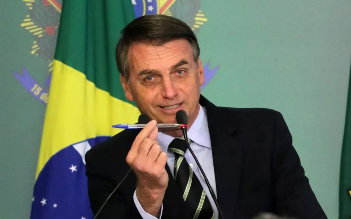 O presidente Jair Bolsonaro assina o decreto que flexibiliza os critérios para a posse de armas no Brasil — Foto: Fátima Meira/Futura Press/Estadão Conteúdo