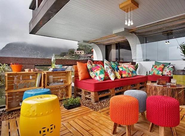 Nesta varanda, projetada pelas arquitetas Andrea Figari e Priscila Bastos, os pallets formam a estrutura do sofá. Caixotes de feira empilhados são aproveitados como estantes e as cores dão vida ao ambiente (Foto: Divulgação)