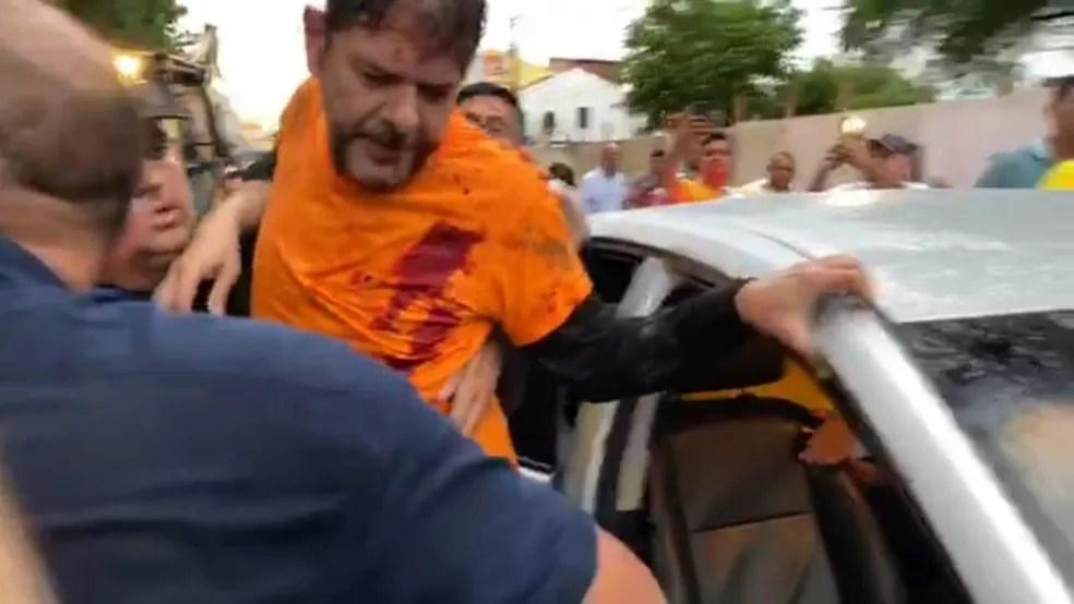 Senador licenciado Cid Gomes (PDT/CE) é levado para carro após ser baleado durante protesto de policial em Fortaleza — Foto: Reprodução