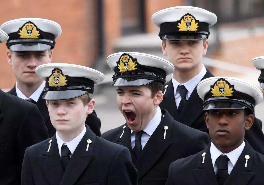 Jovem boceja enquanto aguarda com colegas a visita real da rainha Elizabeth II e do príncipe Philip no Colégio Pangbourne, perto de Reading, na Inglaterra (Foto: Toby Melville/Reuters)