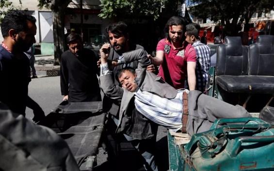 Homens movem um homem ferido para um hospital (Foto: Mohammad Ismail / Reuters)