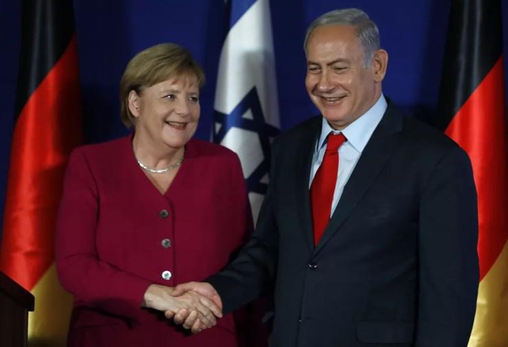 Chanceler alemã Angela Merkel e primeiro-ministro israelense Benjamin Netanyahu apertam as mãos durante coletiva de imprensa nesta quinta-feira (4) em Jerusalém — Foto: Menahem Kahana/ AFP