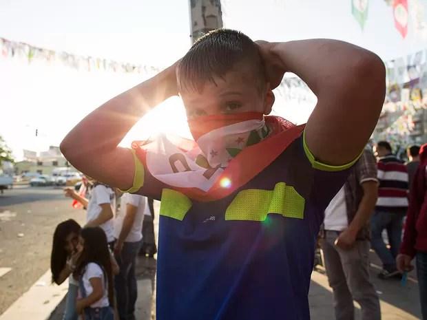 Jovem curdo usa uma das bandeiras do partido HDP (partido que representava os anseios dos curdos nas eleições da Turquia) como máscara, momentos antes de um confronto com a polícia. (Foto: Michel Coeli)