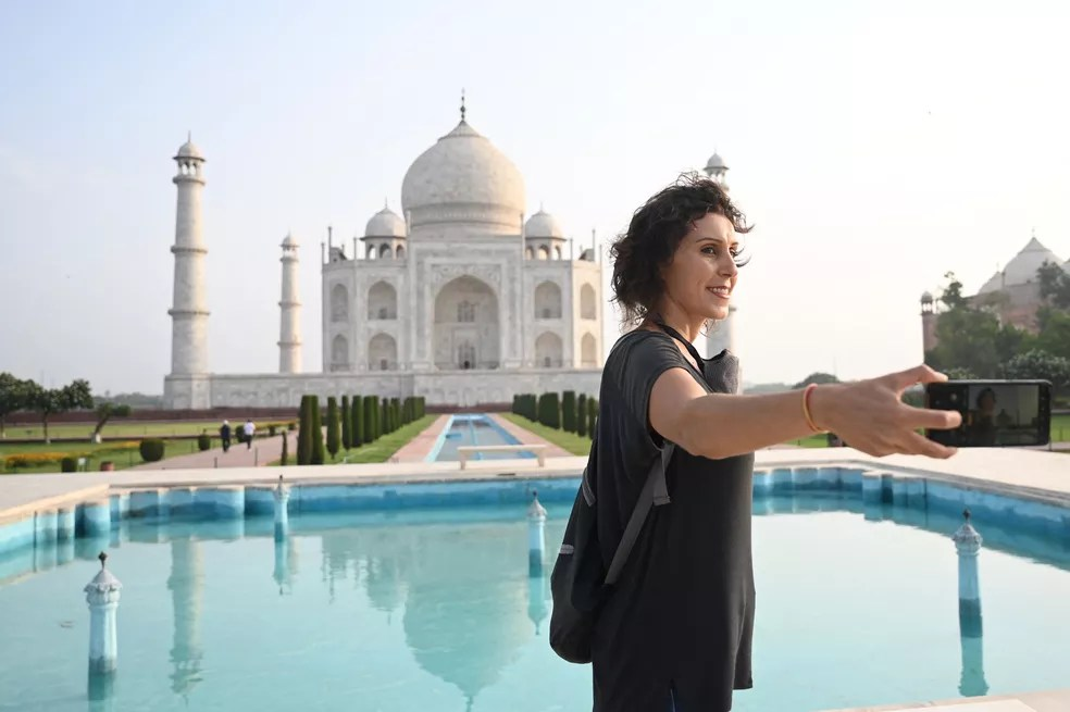 A brasileira Melissa Dalla Rosa tira fotos de lembrança no Taj Mahal no dia da reabertura aos visitantes em Agra, na Índia, em 16 de junho de 2021 — Foto: Money Sharma/AFP