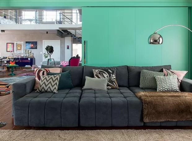 As almofadas que enfeitam o grande e confortável sofá são feitas de lenços da grife Pucci. A porta de correr verde separa o ambiente do living. Ideia da arquiteta Andrea Murao (Foto: Cacá Bratke/Editora Globo)