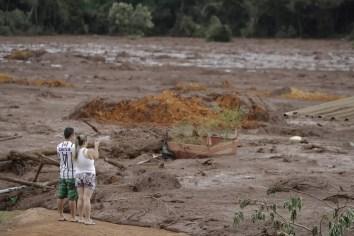 Casal com familiares desaparecidos observa a área inundada após o rompimento da barragem da Vale em Brumadinho. — Foto: André Penner/AP