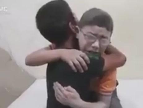 Meninos se abraçam após saber da morte de irmão em ataque em Aleppo, no norte da Síria (Foto: AMC/ Reprodução G1)