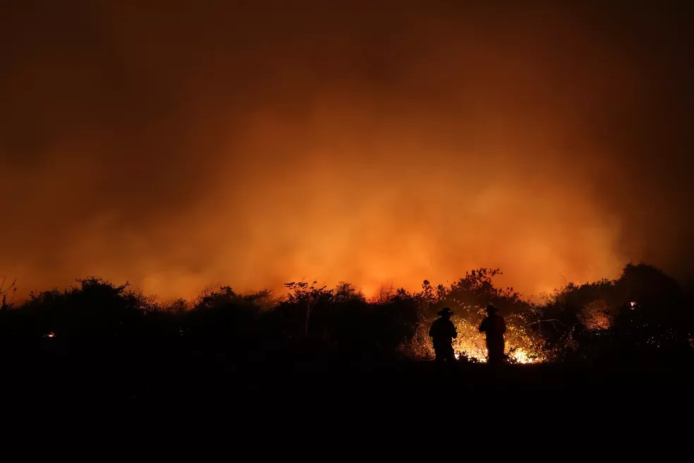 Funcionários de uma fazenda são vistos próximos ao fogo em uma fazenda no Pantanal, em Poconé (MT) — Foto: Amanda Perobelli/Reuters