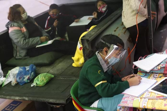 Aluna escreve durante uma aula improvisada em uma caçamba transformada em centro educacional no sul da Cidade do México, no dia 4 de setembro. — Foto: Rebecca Blackwell/AP