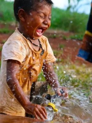 Menino indígena se diverte com a água. (Foto: Daniel Jaeger Vendruscolo / Arquivo pessoal)