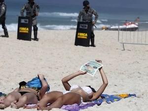 Banhistas tomam sol na praia da Barra da Tijuca, com militares da Força Nacional ao fundo (Foto: Sergio Moraes/Reuters)