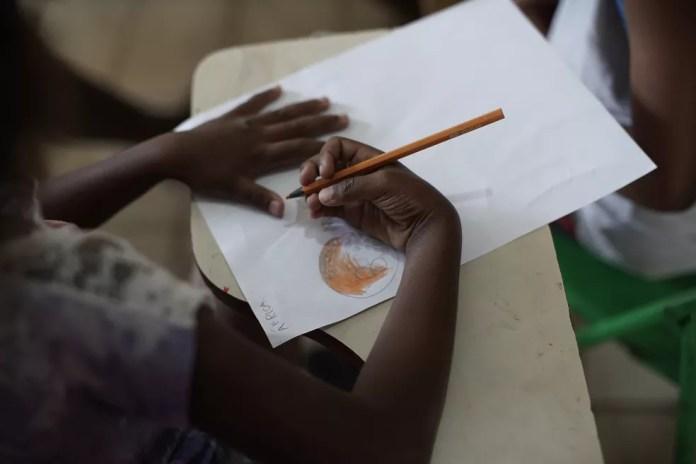 Foto mostra menina colorindo figura em uma biblioteca comunitária na favela do Morro do Salgueiro, no Rio de Janeiro, no dia 27 de agosto. — Foto: Silvia Izquierdo/AP