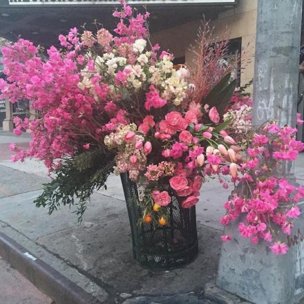 Floral designer is turning NYC trash cans into giant vases overflowing with flowers.