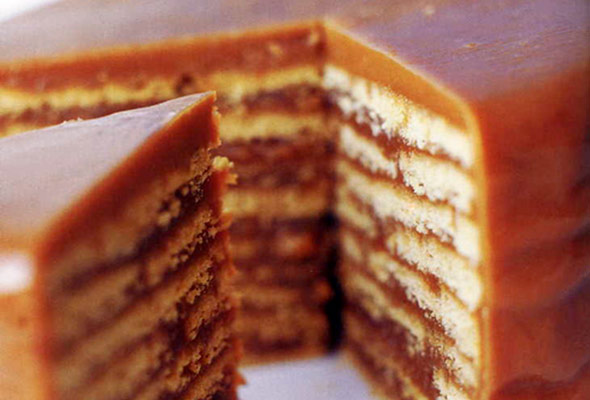 A nine layer butterscotch cake with one slice being removed from it.